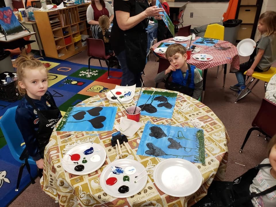 Students painting with their class